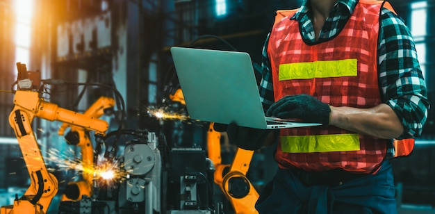 Engineer use advanced robotic software to control industry robot arm in factory