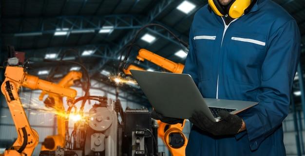 엔지니어는 고급 로봇 소프트웨어를 사용하여 공장에서 산업용 로봇 팔을 제어합니다. 프리미엄 사진