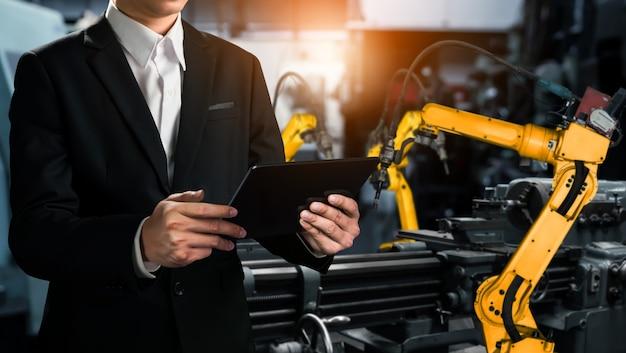Инженер использует передовое роботизированное программное обеспечение для управления промышленным роботом на заводе.