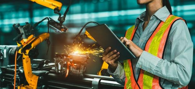 エンジニアは高度なロボットソフトウェアを使用して、工場で産業用ロボットアームを制御します