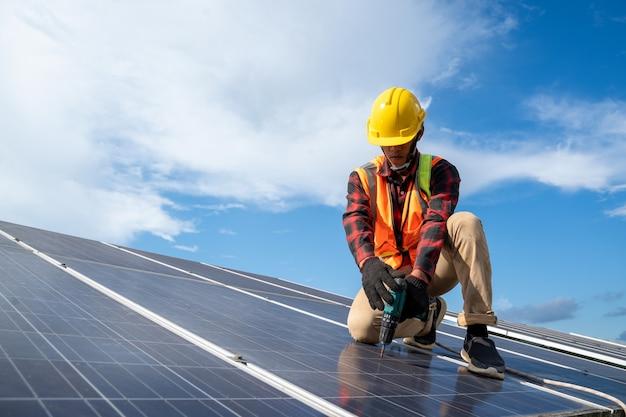 Инженер использует дрель, устанавливая и обслуживая солнечные панели на крыше на солнечной электростанции, инженер работает над заменой солнечной панели, солнечной панели.