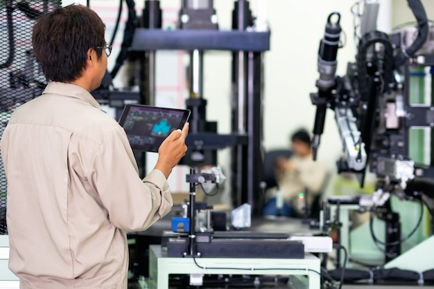 Engineer using digital tablet for testing operation of machine in manufacturing factory plant
