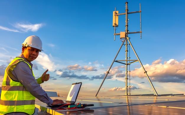Инженер, использующий ноутбук на солнечных батареях на крыше на закате в небе инженер, работающий на фотоэлектрических батареях