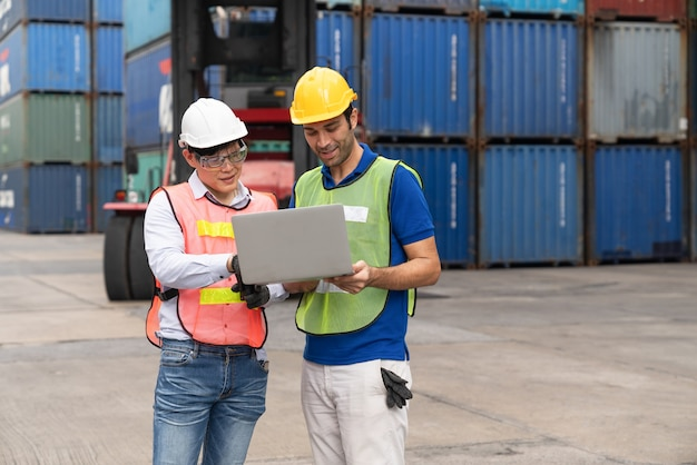 Engineer  using laptop checking position loading containers box at cargo container shipping