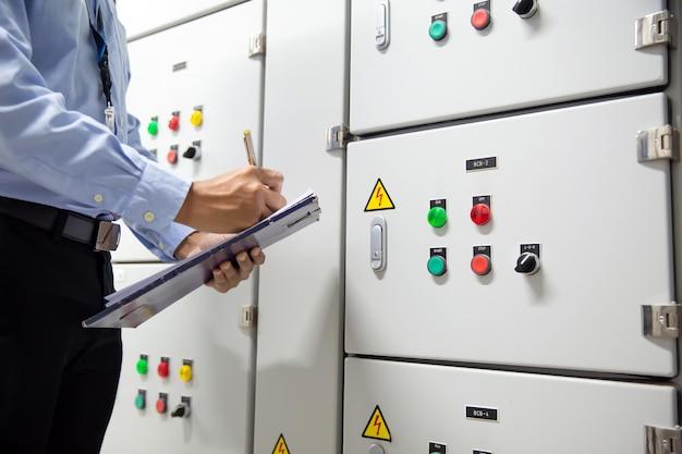 チェックリストを使用して、エアハンドリングユニット(ahu)スターターコントロールパネルのボタンをチェックするエンジニア。