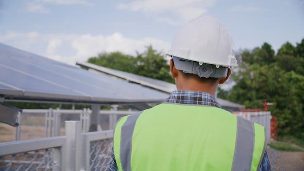 エンジニアは、システムとメンテナンスソーラーパネル、グリーンエネルギー、持続可能な環境の概念をチェックするために太陽電池ステーションを歩き回ります。