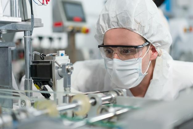 エンジニア着用の衛生マスクは、工場産業で生産中のコロナウイルスチェックマシンを保護します