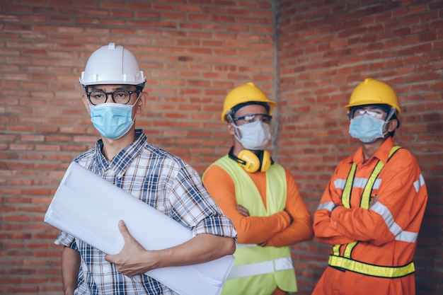 Engineer wear protective face masks safety for coronavirus disease 2019 (covid-19) at construction site,health and construction concept.