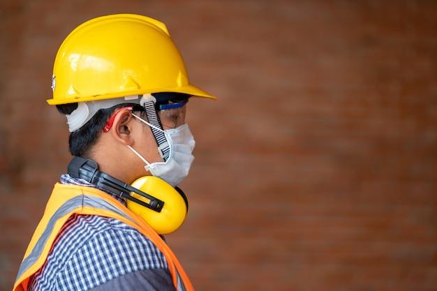 エンジニアは、建設現場で健康と建設のコンセプトでコロナウイルス病2019(covid-19)の保護フェイスマスクの安全を着用します。