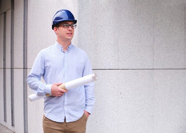Инженер в каске и держит в руке трубку с планами