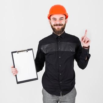 An engineer wearing hardhat holding clipboard gesturing