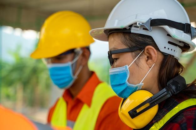 建設現場で働くcovid-19に対して働く保護マスクを身に着けているエンジニア、建築家エンジニア会議の人々のブレーンストーミングのコンセプト。
