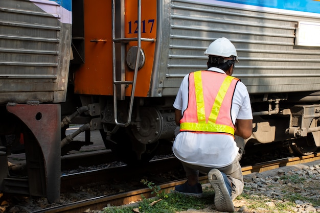 Engineer wearing safety helmet with checking train