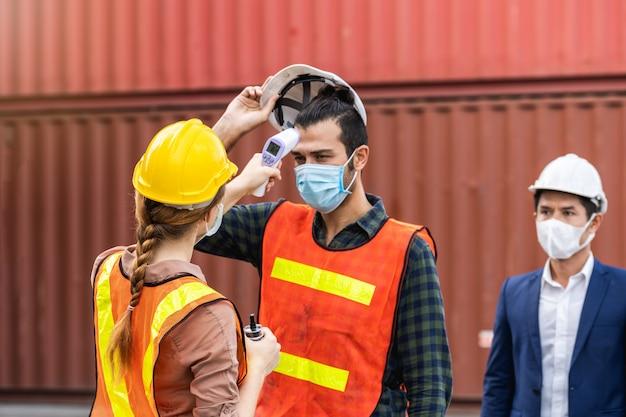 体温をチェックするサージカルマスクを身に着けているエンジニア