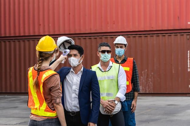 Инженер в хирургической маске проверяет температуру тела