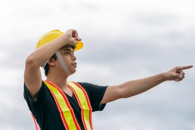 黄色いヘルメットをかぶったエンジニアと彼の手が仕事を指しており、工事を管理しています。
