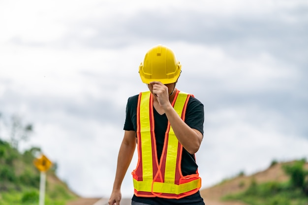 Engineer wearing yellow helmet, controlling the construction.