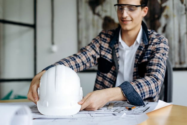 Engineer with hard hat in his hands working in the office