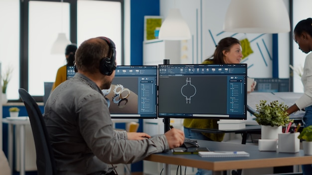 Engineer with headset working on pc screen showing cad software with d construction metalic componen...