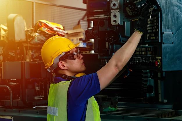 Инженер с защитным шлемом, работающий на заводе