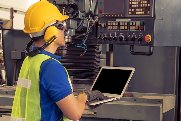 工場で働く安全ヘルメットを持つエンジニア