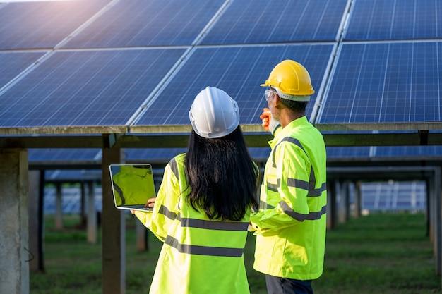 Инженер женщина, держащая цифрового планшета рабочего техника в солнечной электростанции.