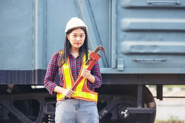 電車のガレージサイトで作業している修理のためのレンチを保持しているエンジニアの女性。