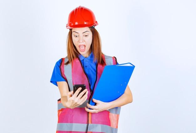 빨간 헬멧을 쓴 엔지니어 여성이 메시지를 확인하거나 화상 통화를 합니다.