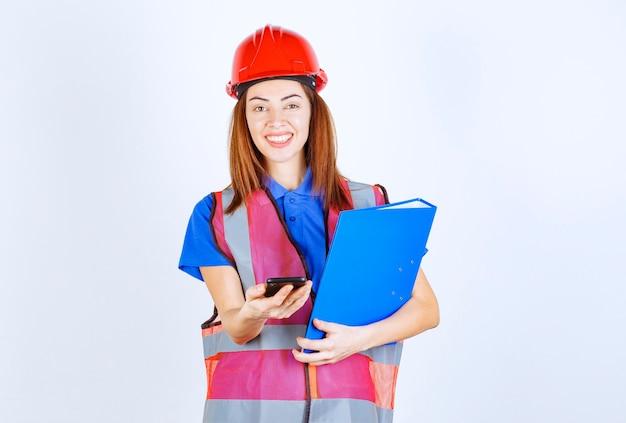 Женщина-инженер в красном шлеме проверяет свои сообщения или делает видеозвонок.