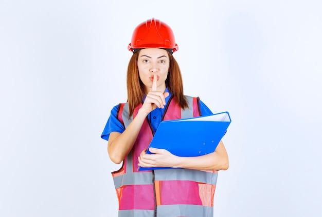 青いプロジェクトフォルダを保持し、沈黙を求めている赤いヘルメットのエンジニアの女性。