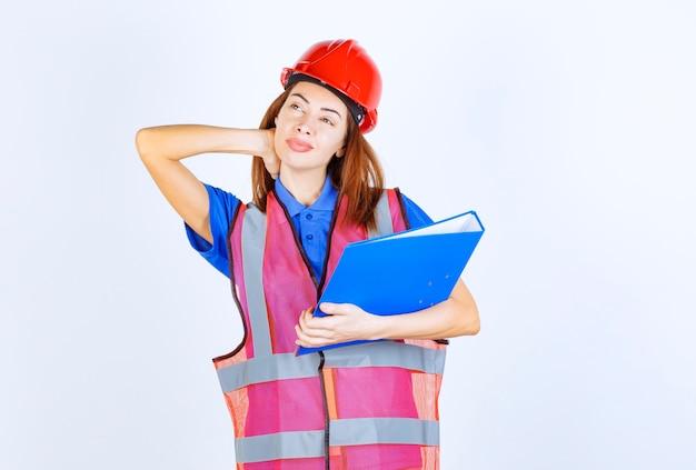 Женщина инженера в красном шлеме держа голубую папку проекта и думая.