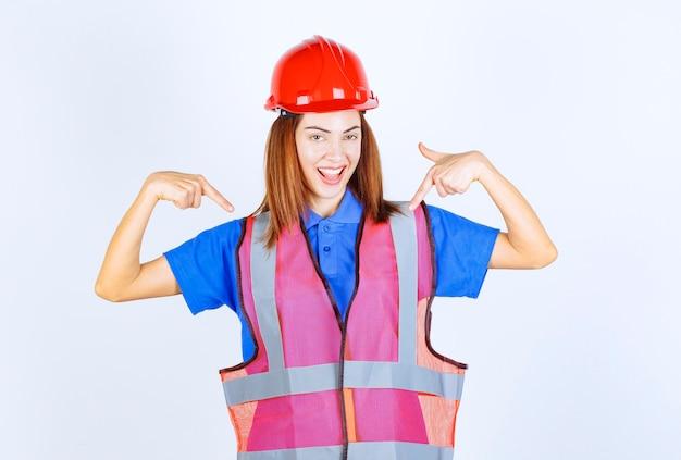 Женщина-инженер в униформе и красном шлеме, представляясь.