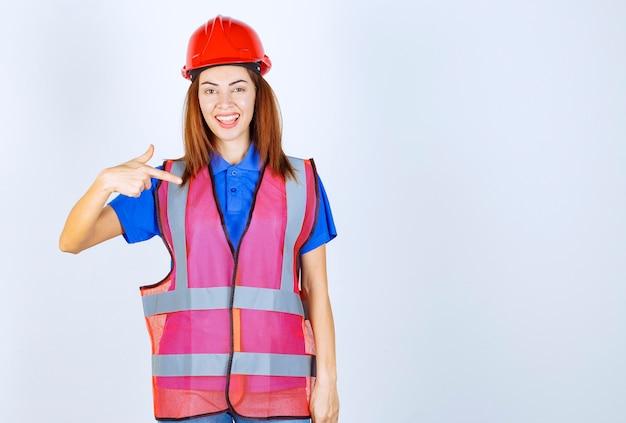 제복을 입은 엔지니어 여성과 자신을 소개하는 빨간 헬멧.