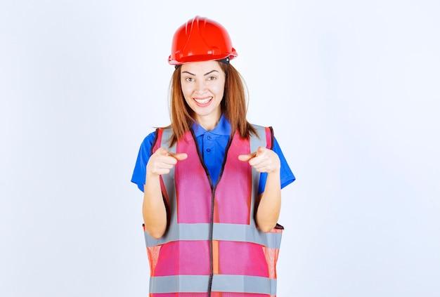 Женщина-инженер в форме и красном шлеме замечает человека впереди.