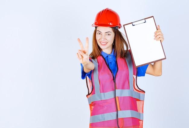 空白のレポートファイルを保持し、満足のサインを示す制服を着たエンジニアの女性。