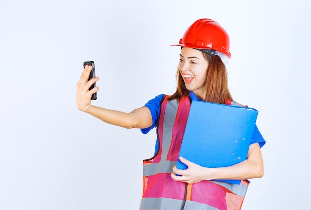 Engineer woman in red helmet checking her messages or making a video call.