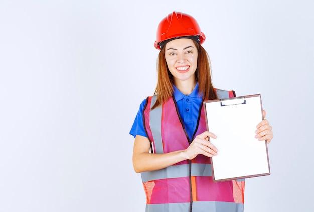 Donna dell'ingegnere in uniforme che tiene un file di segnalazione vuoto.