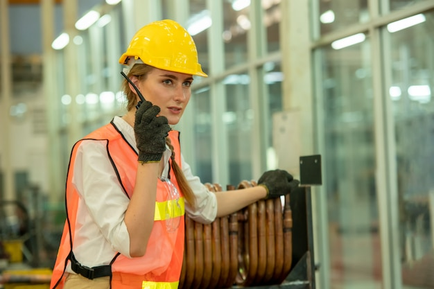 Engineer woman using radio communication at factory, female mechanic use walkie talkie for work.
