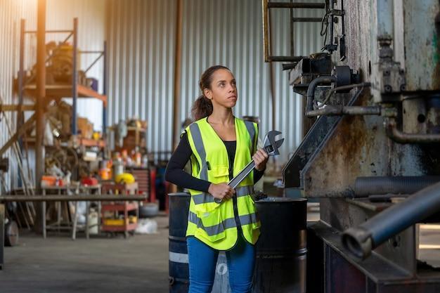 공장에서 실제 작업을 수행하는 보호 제복을 입은 여성 엔지니어.