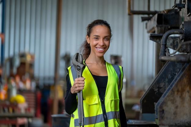 工場で実際の仕事をしている保護制服を着たエンジニアの女性。