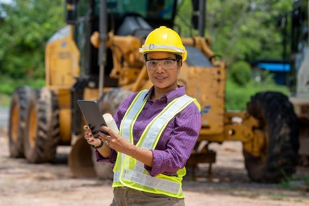 エンジニアの女性は、建設現場での作業にタブレットを使用します。作業エリアでの建設車両の不動産プロジェクト