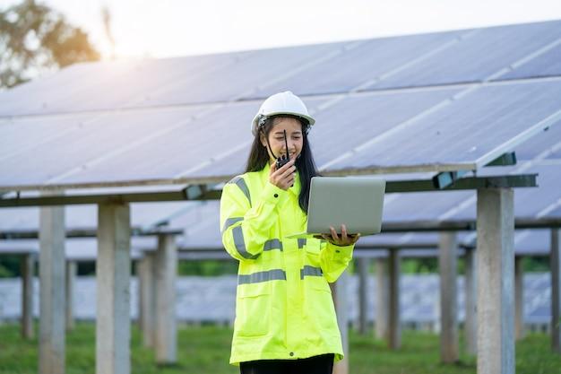 Женщины-инженеры в жилете безопасности и защитном шлеме, держащем портативный компьютер, работающие перед солнечными батареями.