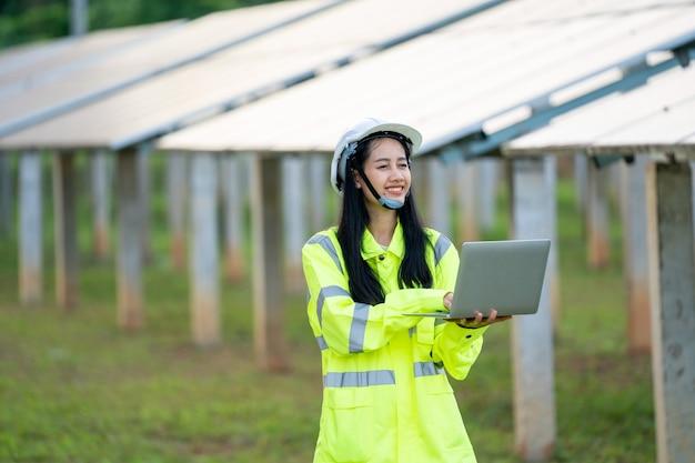 안전 조끼와 태양 전지 패널 앞에서 작업하는 노트북 컴퓨터를 들고 안전 헬멧을 착용하는 엔지니어 여성.