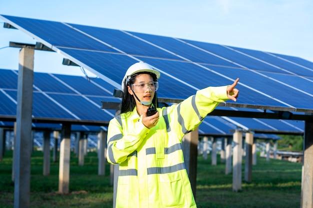 안전 조끼와 안전 헬멧을 착용 한 엔지니어 여성은 라디오를 사용하여 신호를 전달하여 태양 전지판에서 작업합니다.