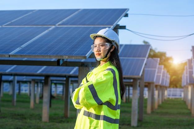 태양 전지 패널 앞에 서있는 안전 조끼를 입고 엔지니어 여성.