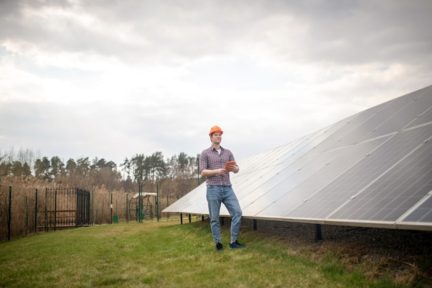 Инженер, работа. молодой взрослый серьезный человек в защитном шлеме с планшетом в руках возле инженерного здания на открытом воздухе во второй половине дня