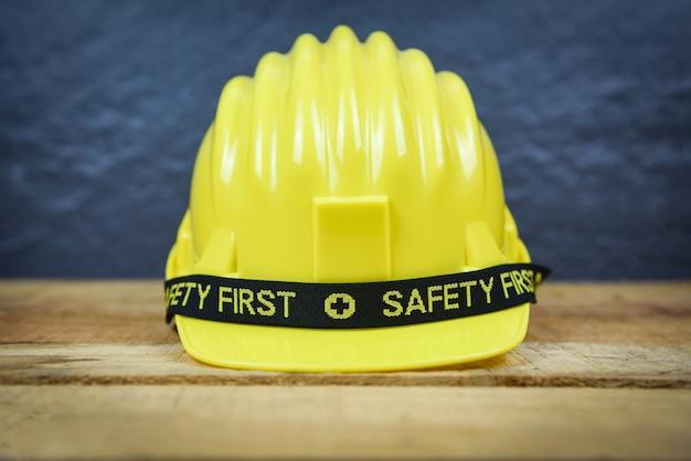 Engineer worker helmet on wooden background - safety first concept yellow hard safety wear helmet hat