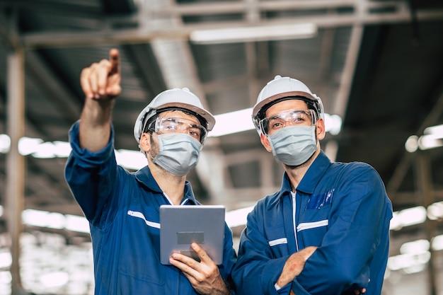 Инженер-рабочий, мужчины, работающие в команде, носят лицевую маску во время работы на заводе, чтобы предотвратить загрязнение воздуха вирусом covid-19 и обеспечить хорошее здоровье.