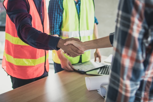 Engineer and worker shake hands before planing and talking construction building