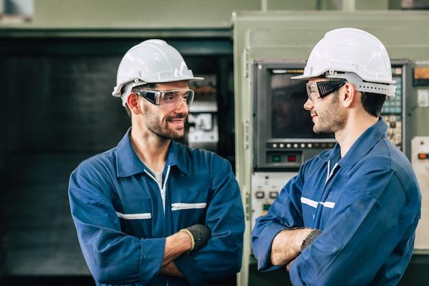 向かい合って立っているエンジニアワーカー。ゲイの労働者が一緒に探しています。